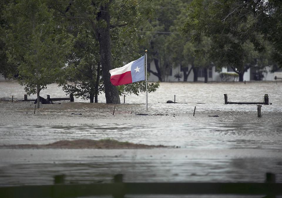 A Texas flag flew over floodwaters in La Grange, Texas, Monday.