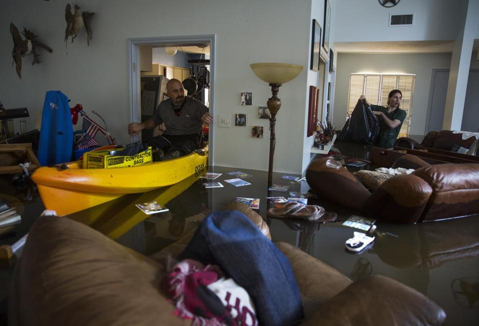 A father and son looked for important papers and heirlooms inside their house after it was flooded by heavy rains from Hurricane Harvey.