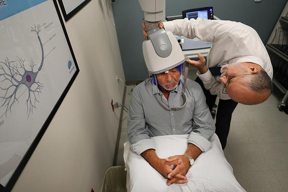 Patient Jerry Peppe, 69, underwent a Transcranial magnetic stimulation (TMS) at McLean Hospital. Next to him is Dr. Oscar Moraes.