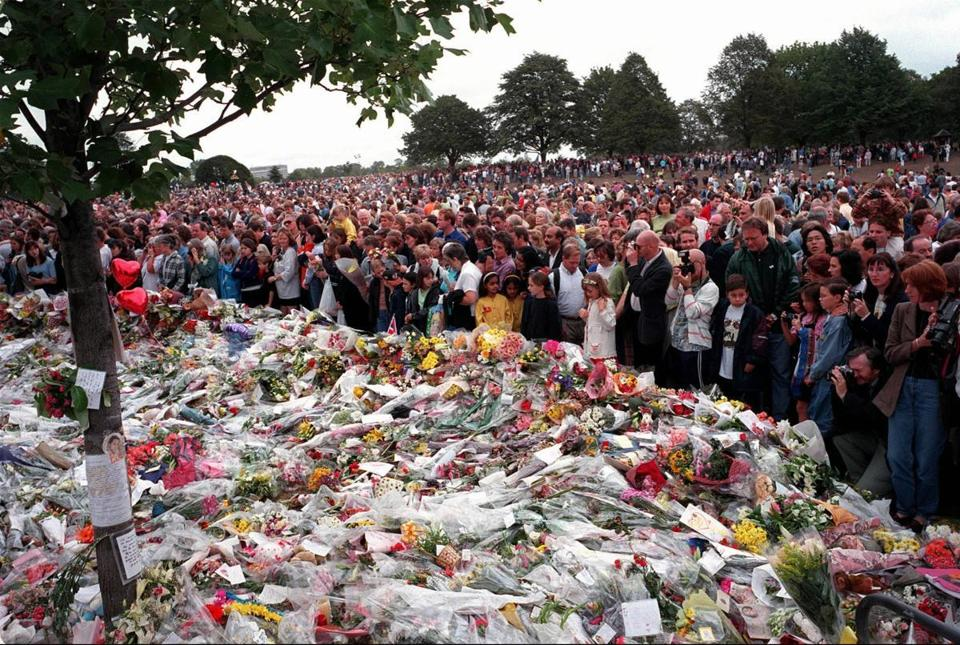 A sea of people crowded around the enormous carpet of flowers deposited by mourners at the gates of Diana the Princess of Wales' former residence in London.