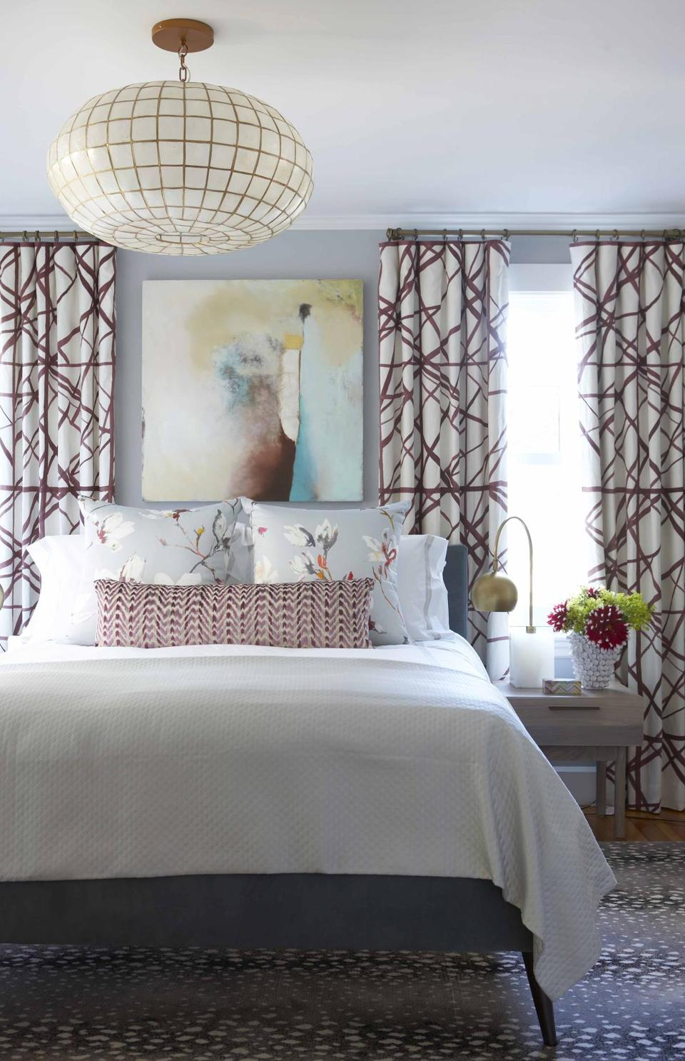 In the master bedroom, maroon-and-white patterned drapes by Kelly Wearstler for Lee Jofa add modern flair. An antelope-print rug from Landry & Arcari feels lush underfoot; the bold Capiz-shell-and-brass light fixture is by Serena & Lily.