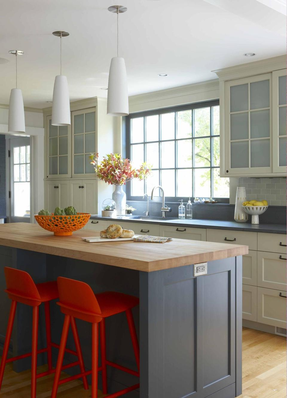 A 400-square-foot addition allowed for an expanded kitchen area, made cheery with accents of vibrant orange paired with dark blue.