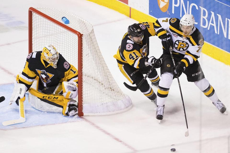 The Providence Bruins' Sean Kuraly sends the puck past the Wilkes-Barre/Scranton Penguins' Barry Goers as Casey DeSmith defends the goal during Game 5 of the AHL Atlantic Division hockey series in Wilkes-Barre, Pa., Sunday, April 30, 2017. (Christopher Dolan/The Citizens' Voice via AP)