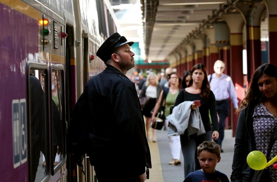 A conductor watches commuters board a train at South Station.