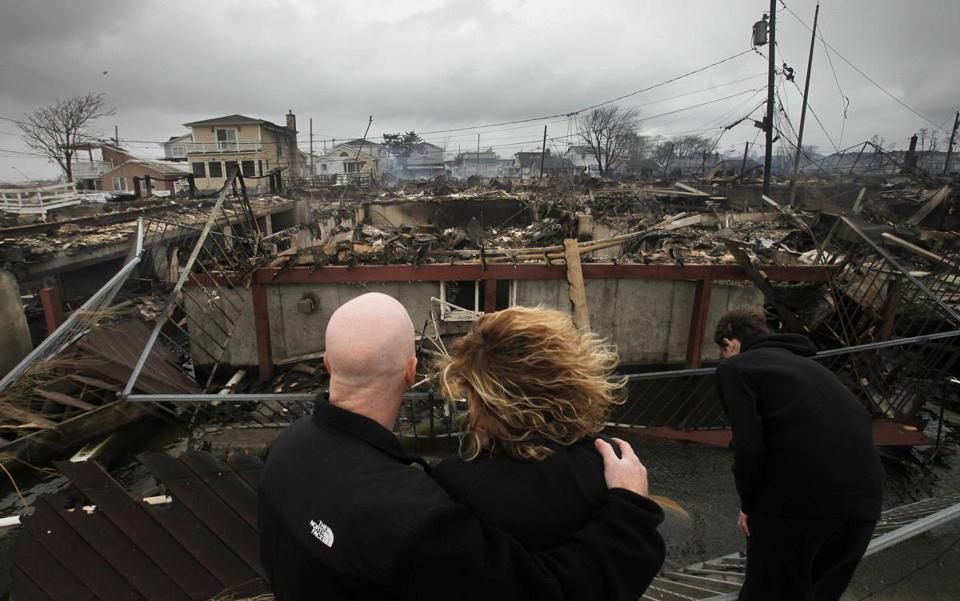 Robert Connolly, left, embraced his wife Laura as they survey the remains of the home owned by her parents that burned to the ground in the Breezy Point section of N.Y.