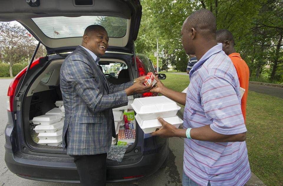Pastor Elysee Isidor (left) handed out boxes of food to Haitian asylum seekers in a park next to Olympic Stadium. Isidor and his wife bring food every day.