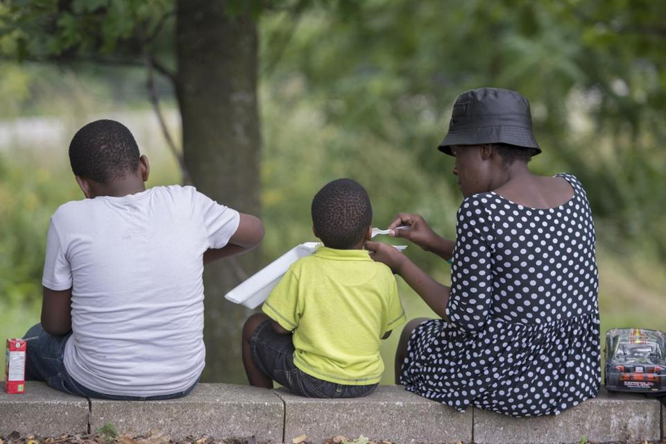 A woman and two children ate food handed out by an evangelical church in a park next to the Olympic Stadium in Montreal.