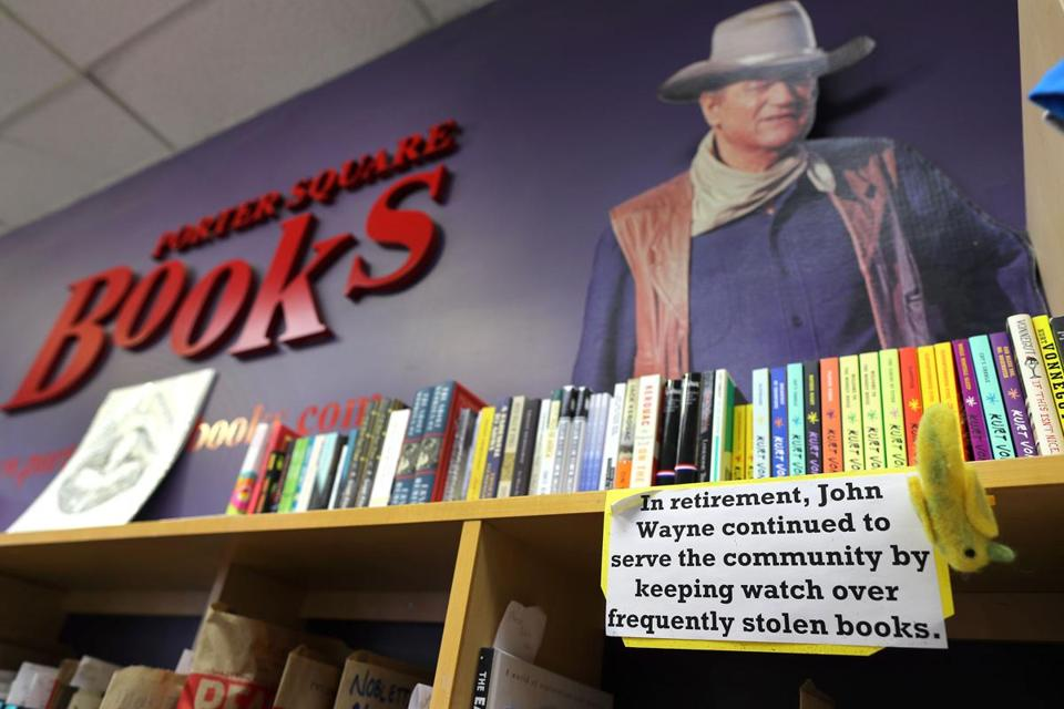 John Wayne keeps an eye on things at Porter Square Bookstore, which has contended with thieves making off with books.
