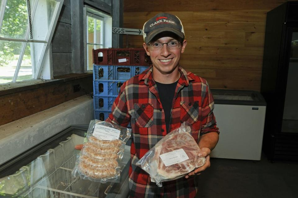 Farm employee Kyle Bonenfant displays sausages and a pork roast, two of many meat products that are sold to customers. This is a pick-up day at Clark Farm in Carlisle, where people buy CSA shares and get back farm products throughout the season. Jon Chase for the Boston Globe
