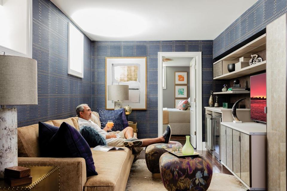The blue Phillip Jeffries grass-cloth wallcovering is embellished with gold accents that play off the glossy gilt Bernhardt side tables. The custom sofa is by Kravet, and the floral print ottomans, from Moss Studio, serve as both footrests and cocktail tables.