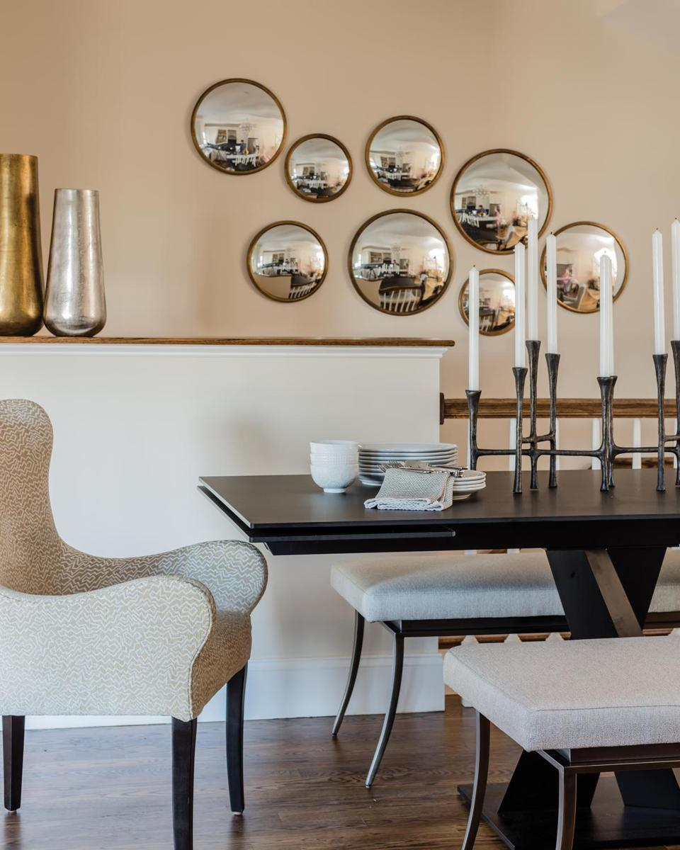 The slim black Roche Bobois trestle table had the perfect silhouette for the narrow dining area; it also expands when needed for large gatherings. The benches are from Cabot House, and the upholstered host chairs are by Lee Industries. A mirror collage helps make the space feel bigger.