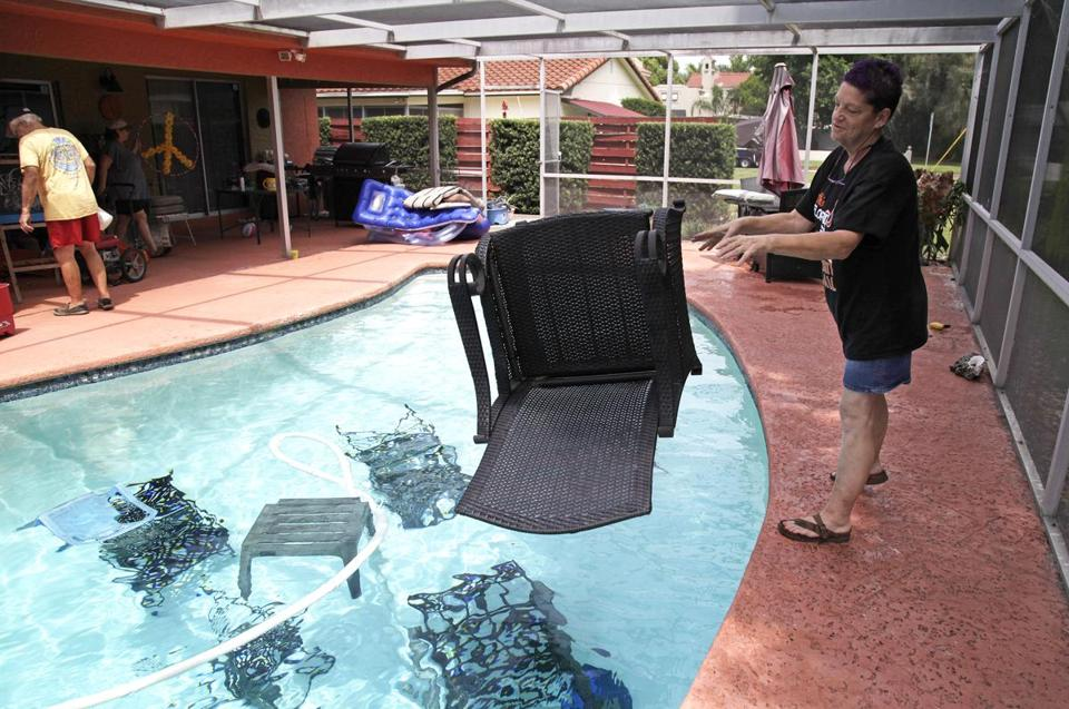 Jackie Kreuter, 56, of Gulfport, Fla., tossed pool furniture in the pool Tuesday so it doesn't fly around during the impending hurricane.