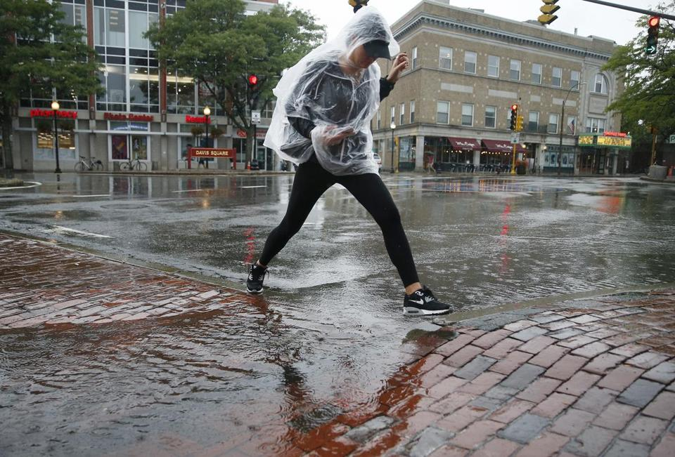 A woman hopped over a puddle after a heavy rain fell in Davis Square on Wednesday