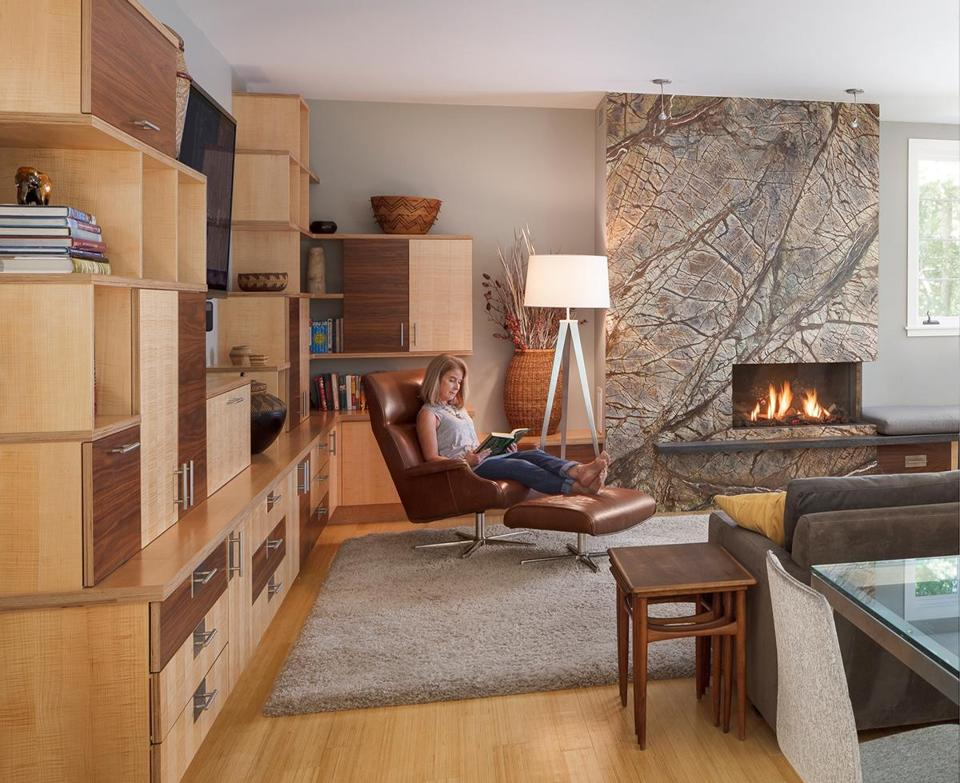 In the family room, homeowner Catherine Riedel relaxes in a leather Beau chair from Room & Board. Architect Gary Wolf designed the custom cabinetry; the exposed edges contribute to the modern feel. Each child has a cabinet to store schoolbooks; a charging drawer corrals electronic devices.