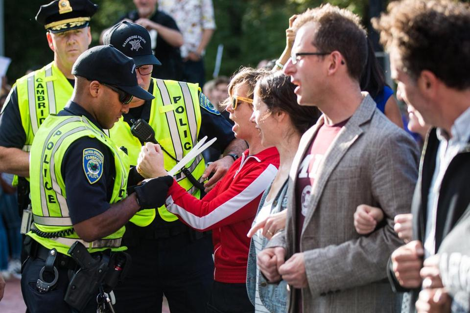 Cambridge police officers arrested professors after they locked arms and shut down Massachusetts Avenue next to Harvard University while protesting the removal of DACA.