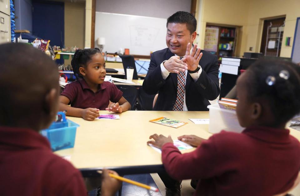 "Boston, MA - 9/72017 - Superintendent Tommy Chang (cq) shows a ""magic trick"" to 6-year-old Kiary Marcelin (cq), center, and some of her first-grade classmates. Boston Mayor Martin J. Walsh (cq) and Chang visit the Young Achievers Science & Math Pilot K-8 (cq), on the first day of school. Photo by Pat Greenhouse/Globe Staff Topic: 08BPS Young Achievers Reporter: XXX"