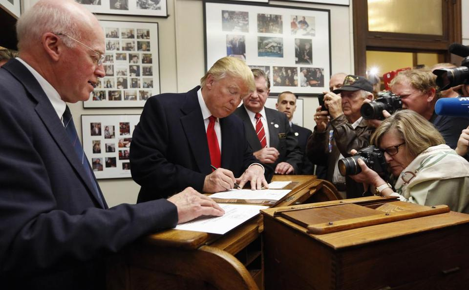 New Hampshire Secretary of State Bill Gardner (left) watched in November 2015 as then-candidate Donald Trump filled out his papers to be on the nation's earliest presidential primary ballot.