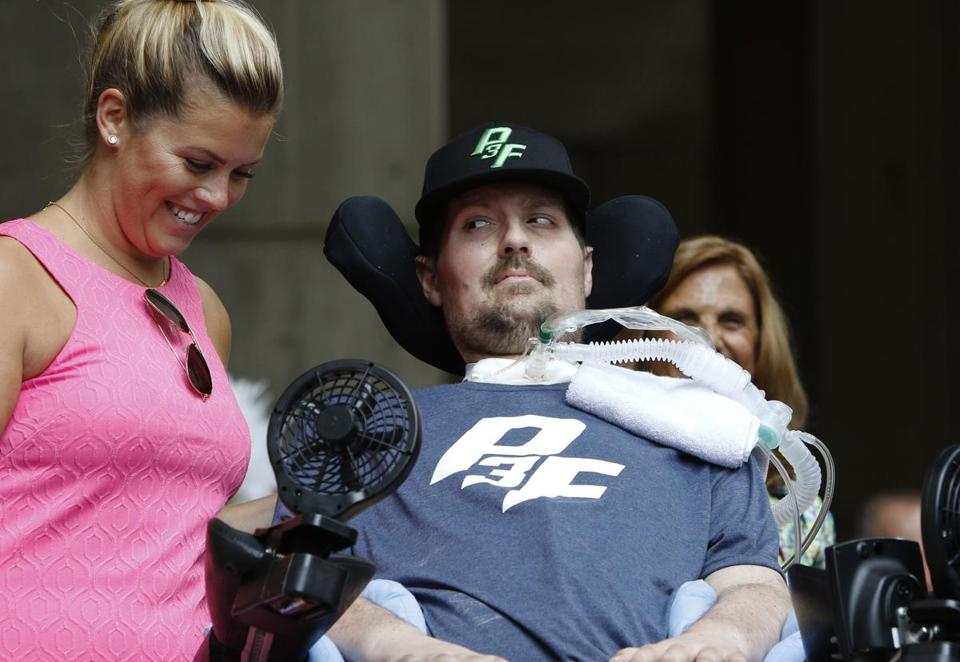 Pete Frates, right, who inspired the ice bucket challenge, looks at his wife Julie is during a ceremony at City Hall in Boston where Tuesday, Sept. 5, 2017, was declared Pete Frates Day by Boston Mayor Marty Walsh. (AP Photo/Bill Sikes)