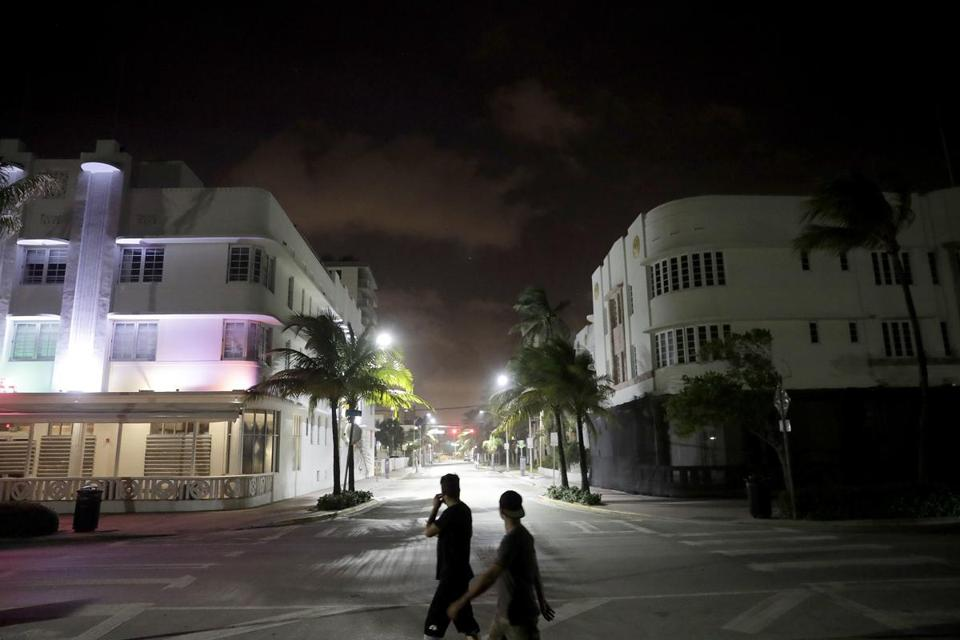 Pedestrians walk through the usual bustling South Beach ahead of Hurricane Irma in Miami Beach, Fla.