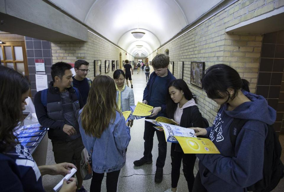 A group of foreign students browsed a brochure while touring the University of Toronto campus.