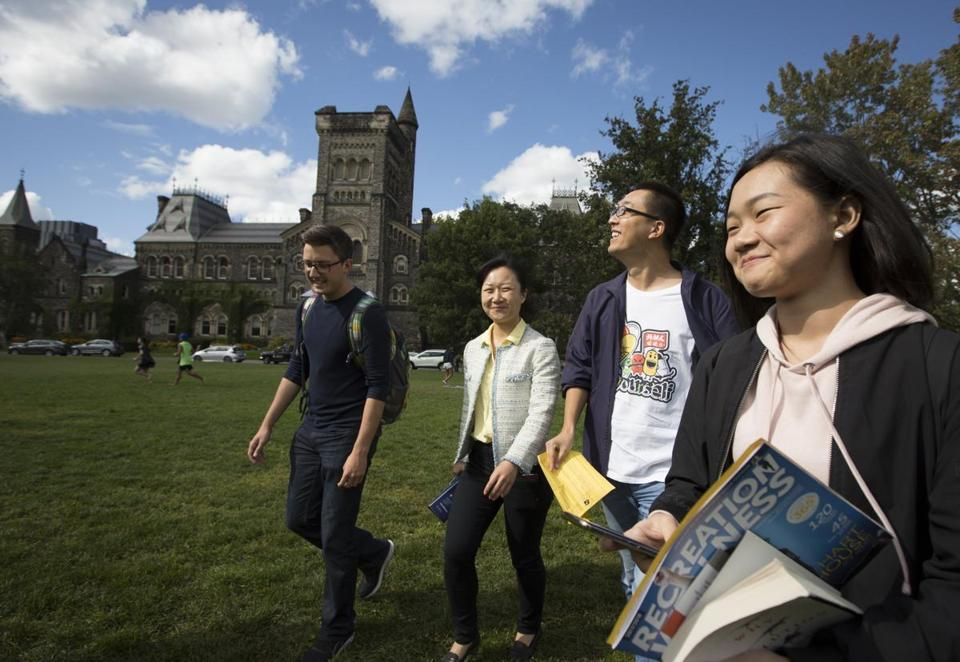 A group of students new to the University of Toronto walked across the lawn after a campus tour.