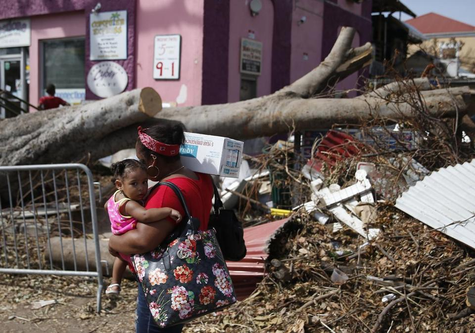 A woman carried a child and emergency water Tuesday as she passed debris from Hurricane Irma strewn in Cruz Bay, Virgin Islands.