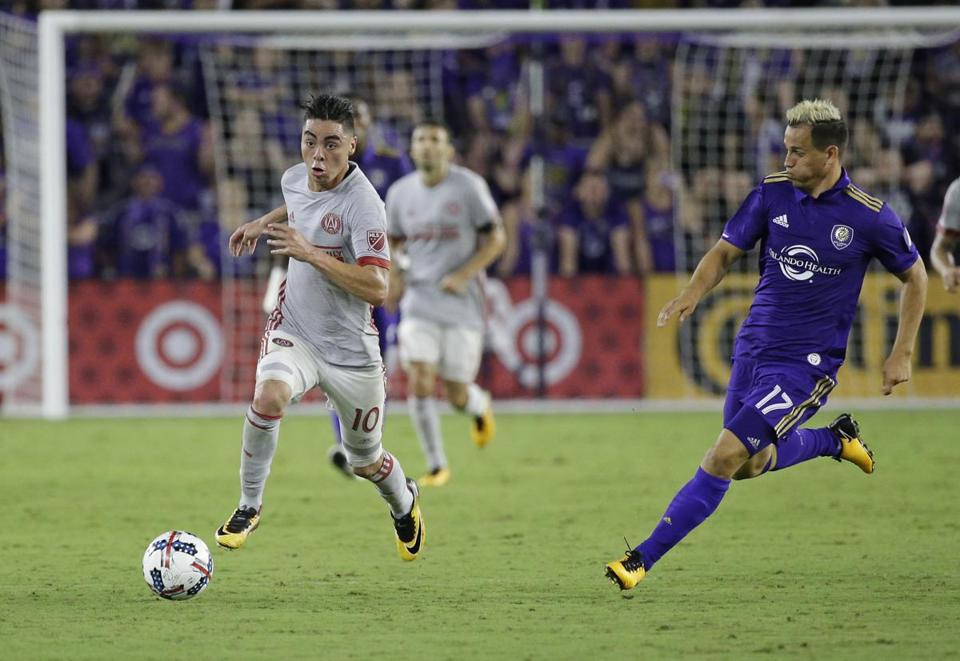 Atlanta United's Miguel Almiron (10) moves the ball past Orlando City's Luis Gil during the second half of an MLS soccer match, Friday, July 21, 2017, in Orlando, Fla. Atlanta United won 1-0. (AP Photo/John Raoux)