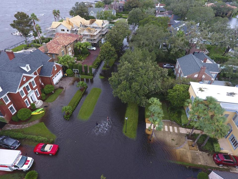 In this Monday, Sept. 11, 2017, photo provided by DroneBase, people trudge through floodwaters in the aftermath of Hurricane Irma in Jacksonville, Fla. In a parting blow to the state, the storm caused record flooding in the Jacksonville area. (DroneBase via AP)
