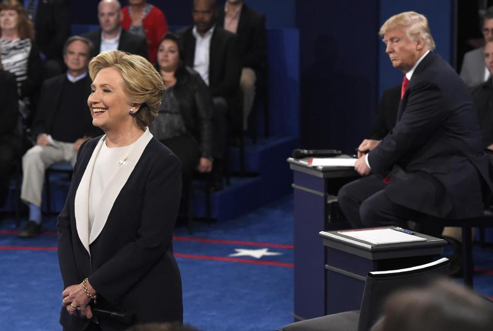 Hillary Clinton speaks as Donald Trump looks on, at the second presidential debate, Oct. 9, 2016.