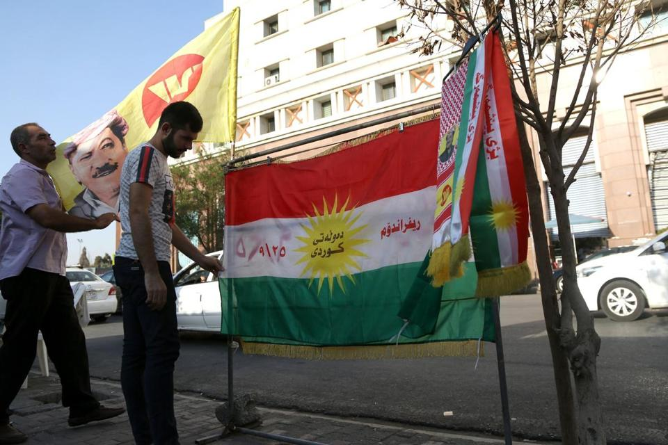 Two Kurdish men hang posters and flag with the picture of the president of the Iraqi Kurdistan Region Masoud Barzani, to encourage Kurdish people to vote in the upcoming independence referendum.