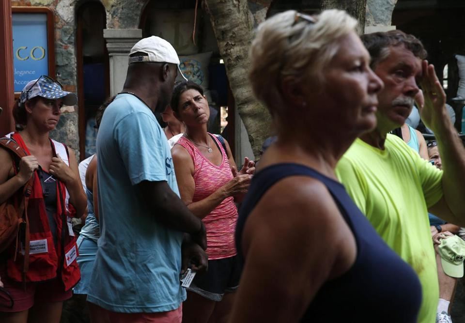 People listen to information about evacuations and updates about the current situation on the island during a community meeting held at Mongoose Junction in Cruz Bay, St. John.