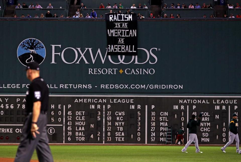 Boston, MA - 9/13/2017 - (4th inning) A banner protesting racism is unfurled over the Green Monster during the fourth inning. The Boston Red Sox host the Oakland Athletics in the second of a three game series at Fenway Park. - (Barry Chin/Globe Staff), Section: Sports, Reporter: Peter Abraham, Topic: 14Red Sox-A's, LOID: 8.3.3712452174.