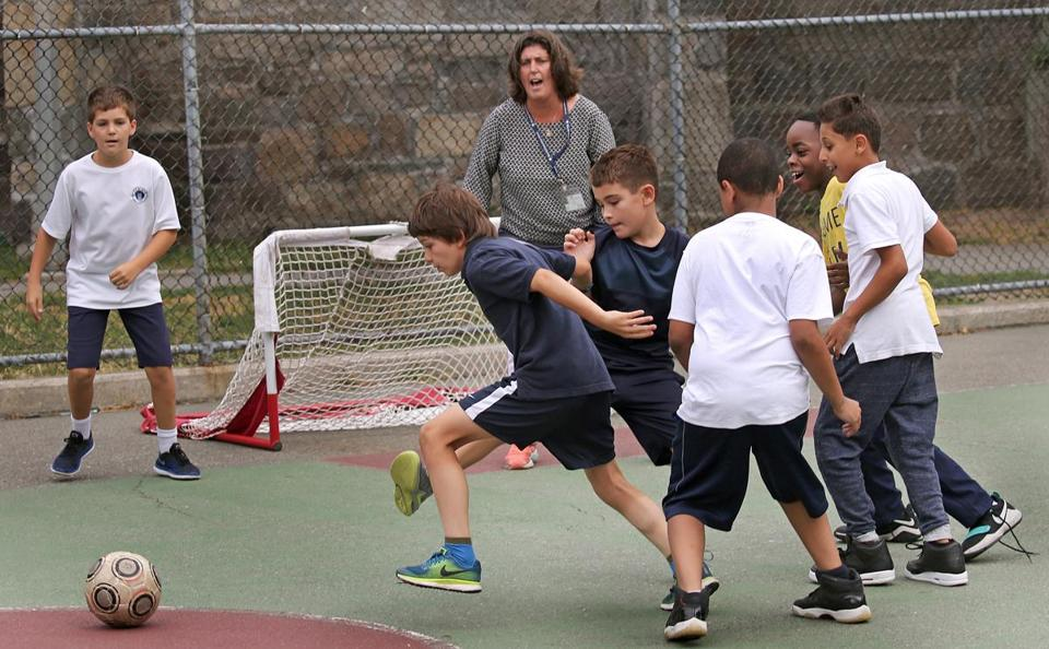 Eliot School students played soccer with principal Traci Walker Griffith guarding the net during recess.