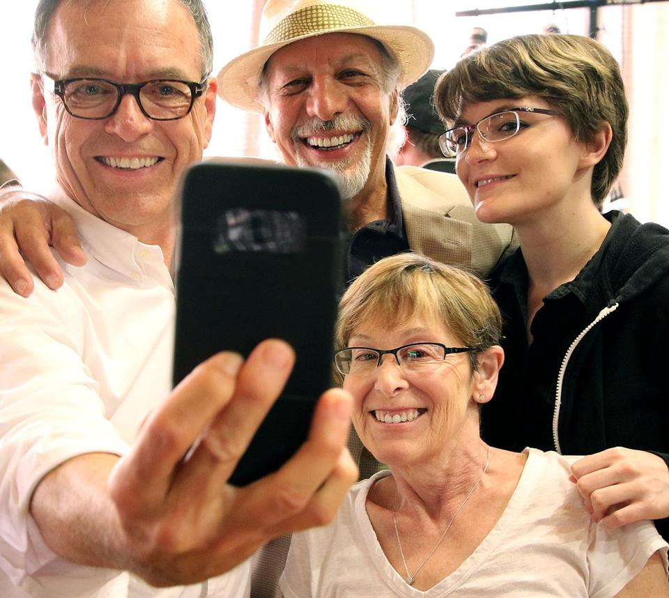 Hollywood character actor Erick Avari, wearing hat, takes a group photo with fans, Larry Murphy, his wife, Hilari, and their daughter, Nataliya, during Avari's stop at the Noshery in Amesbury. He's been traveling around the country with his dog, talking to groups about kindness. Mark Lorenz for the Boston Globe.
