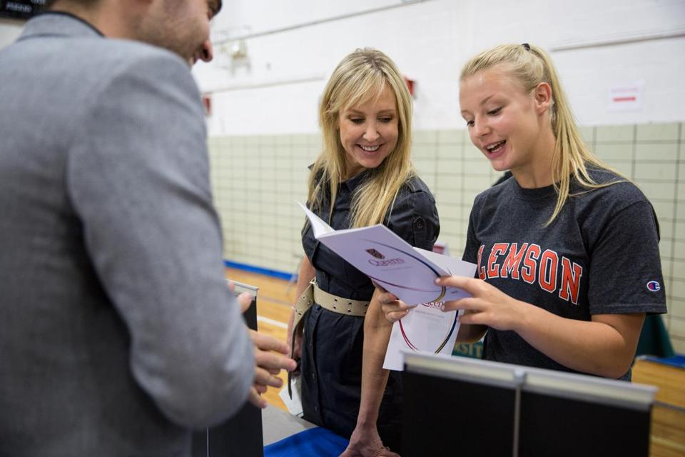 Prospective student Raisa Jarostchuk, 16, (right) and mother Karen Jarostchuk, (center) spoke with recruiter Michael Benincasa of Queens University, during the EduCanada fair, held at the International School of Boston.