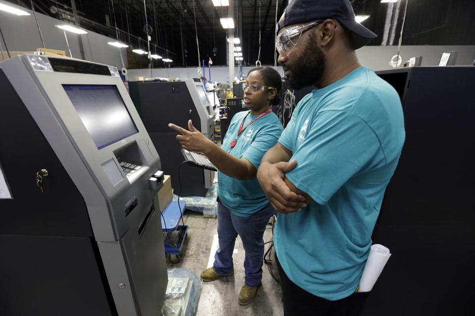 Diebold Nixdorf employees Stephen Cheek and Lashanda Mitchell checked out ATMs at the firm's factory.