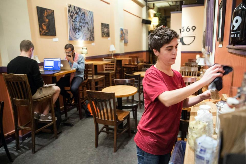 Assistant general manager Caroline Drozdiak cleans up after closing while patrons linger at 1369 Coffee House in Central Square in Cambridge.
