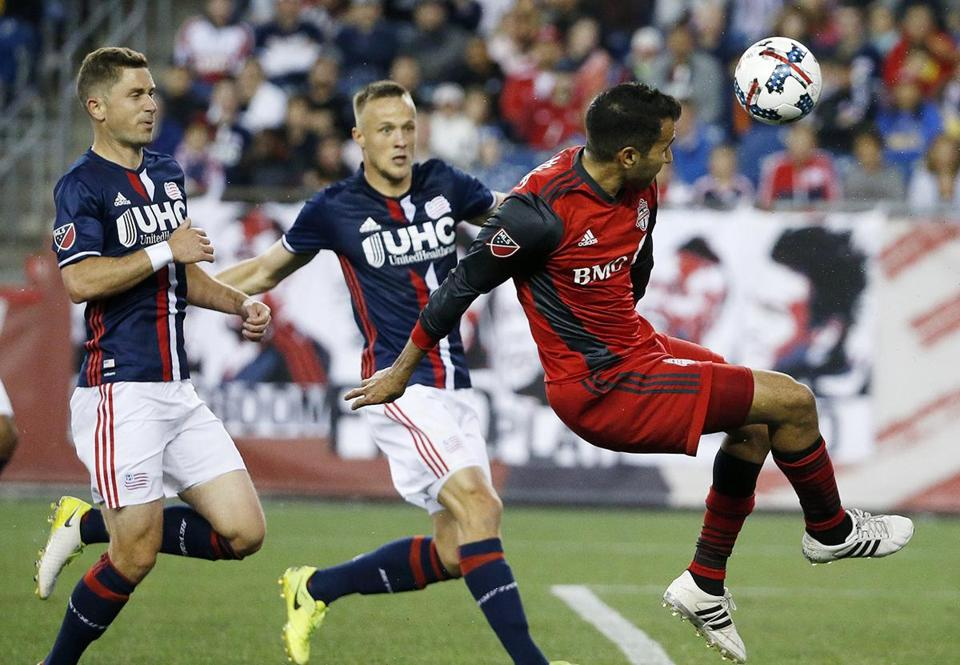 Toronto FC's Steven Beitashour, right, centers the ball in front of New England Revolution's Antonio Delamea Mlinar, center, and Chris Tierney, left, during the first half of an MLS soccer match, Saturday, June 3, 2107, in Foxborough, Mass. The Revolution won 3-0. (AP Photo/Michael Dwyer)