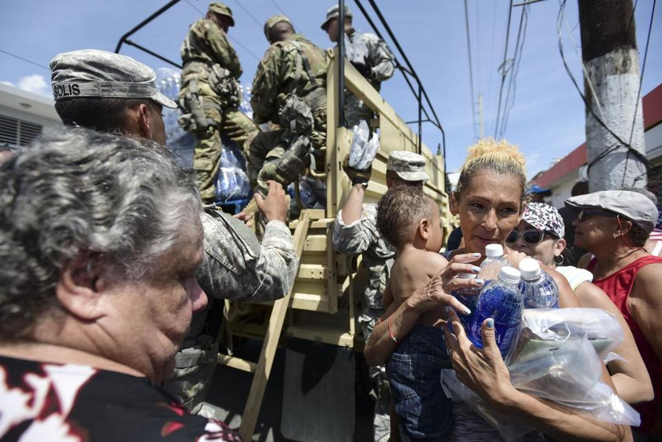 In this Sept. 24, 2017, photo, National Guard Soldiers arrive at Barrio Obrero in Santurce to distribute water and food among those affected by the passage of Hurricane Maria, in San Juan, Puerto Rico. Federal aid is racing to stem a growing humanitarian crisis in towns left without fresh water, fuel, electricity or phone service by the hurricane. (AP Photo/Carlos Giusti)
