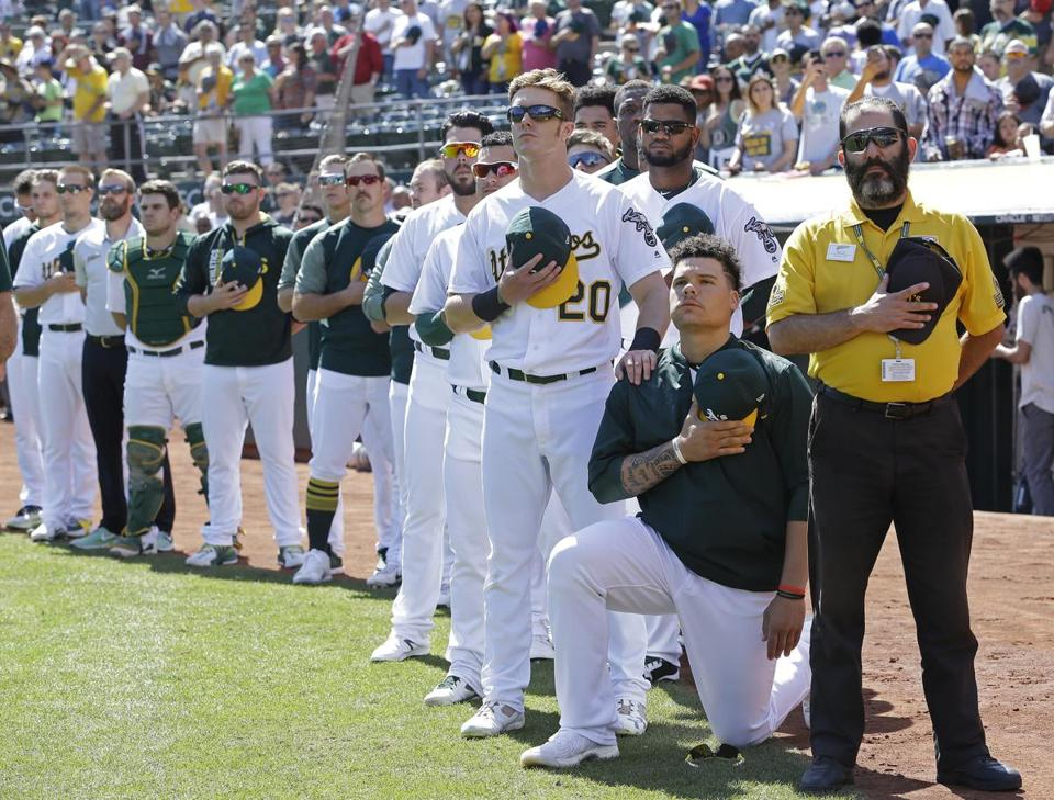 FILE - In this Sunday, Sept. 24, 2017, file photo, Oakland Athletics' Mark Canha (20) places his hand on the shoulder of Bruce Maxwell as Maxwell takes a knee during the national anthem prior to a baseball game against the Texas Rangers in Oakland, Calif. What began more than a year ago with a lone NFL quarterback protesting police brutality against minorities by kneeling silently during the national anthem before games has grown into a roar with hundreds of players sitting, kneeling, locking arms or remaining in locker rooms, their reasons for demonstrating as varied as their methods. (AP Photo/Ben Margot, File)