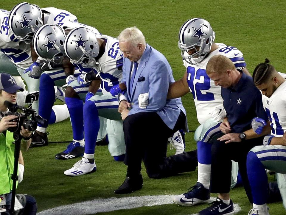 The Dallas Cowboys, led by owner Jerry Jones, center, took a knee prior to the national anthem Monday.