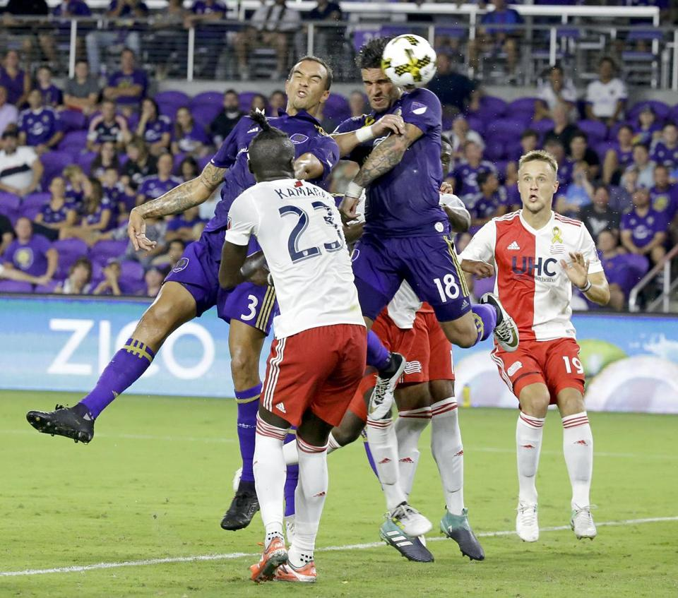 Orlando City's Seb Hines (3) and Dom Dwyer (18) try to head the ball toward the goal off a corner kick, between New England Revolution's Kei Kamara (23) and Antonio Mlinar Delamea (19) during the first half of an MLS soccer match, Wednesday, Sept. 27, 2017, in Orlando, Fla. (AP Photo/John Raoux)