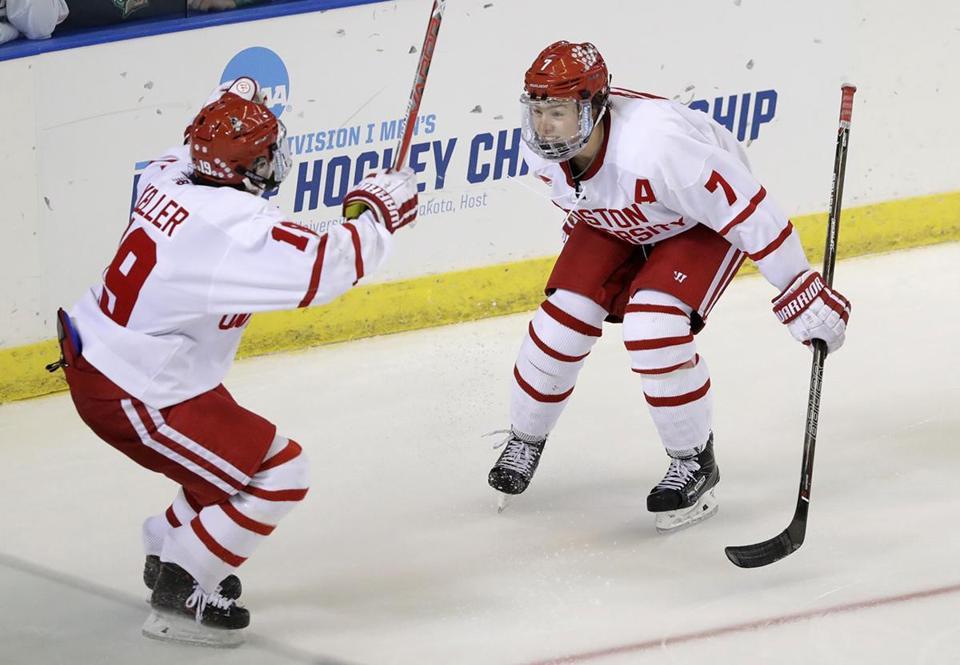 Boston University defenseman Charlie McAvoy (7) skates to forward Clayton  Keller (19) d68a82b3a