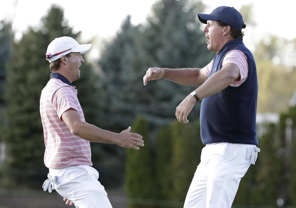 Phil Mickelson, right, celebrates after making his putt on the 18th hole with Kevin Kisner during the four-ball golf matches on the second day of the Presidents Cup at Liberty National Golf Club in Jersey City, N.J., Friday, Sept. 29, 2017. Mickelson and Kevin Kisner won their match against Jason Day and Marc Leishman. (AP Photo/Julio Cortez)