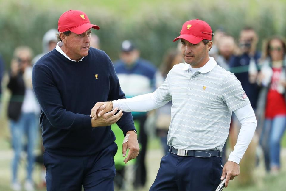JERSEY CITY, NJ - SEPTEMBER 30: Phil Mickelson (L) and Kevin Kisner of the U.S. Team celebrate on the 17th green after defeating Emiliano Grillo of Argentina and the International Team and Jhonattan Vegas of Venezuela and the International Team 2&1 during Saturday foursome matches of the Presidents Cup at Liberty National Golf Club on September 30, 2017 in Jersey City, New Jersey. (Photo by Rob Carr/Getty Images)