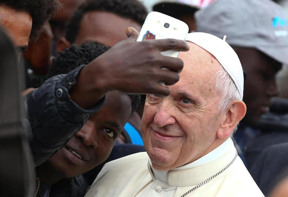 Pope Francis posed for a selfie at a regional migrant center in Bologna, Italy.