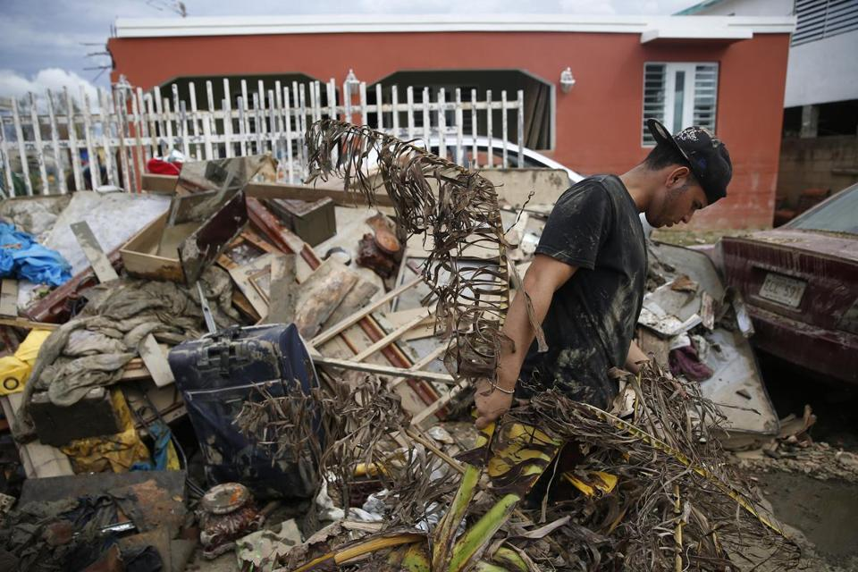 Kened Joel Torres, 18, pulls debris out of his home and onto a growing pile on the street after Hurricane Maria.