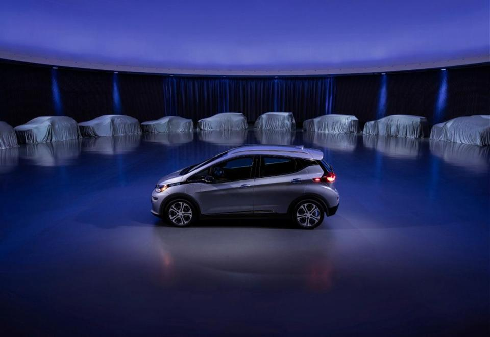 A Chevrolet Bolt, surrounded by nine electric and fuel-cell vehicles covered by tarps.