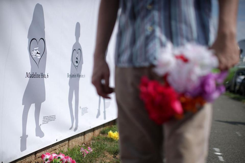 "FAIRFAX, VA - JULY 14: Artist Walt Boyle holds flowers in front of his art piece ""Reflections of Ourselves,"" a makeshift memorial for Sandy Hook victims, during a gun-control rally outside the headquarters of National Rifle Association July 14, 2017 in Fairfax, Virginia. Women's March holds a two-day rally and march from the NRA headquarters to the Justice Department in Washington, DC, to protest the association's ""incendiary and racist actions."" (Photo by Alex Wong/Getty Images)"
