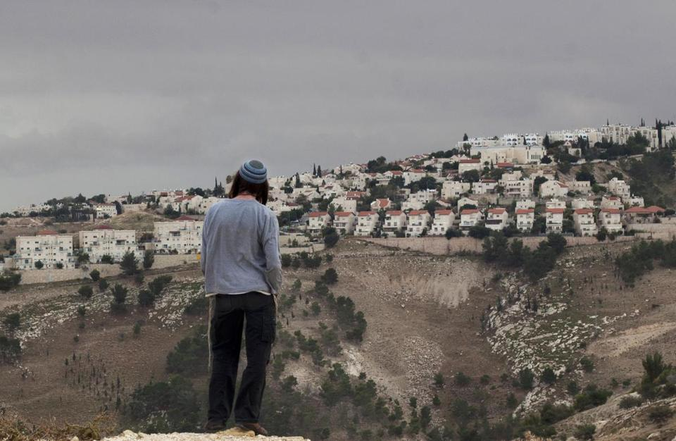 A Jewish settler looked at the West Bank settlement of Maaleh Adumim from the eastern outskirts of Jerusalem. Israel's prime minister on Tuesday pledged to build thousands of new homes in the settlement and annex it to Israel.